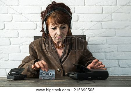Old school music player radio. Spy and operator. Granny dj in headset with cassette player. Old woman with cassette recorder listen music in headphones. Audio book and new technology education.