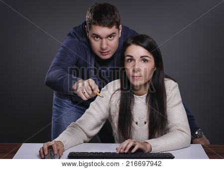 Girlfriend is obstructing her boyfriend while he is trying to watch adult content online by covering his eyes with her hand. Annoyed girlfriend