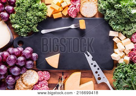 Meat and Cheese plate with a black cutting board. Various cheeses and meats are displayed with kale and purple grapes.
