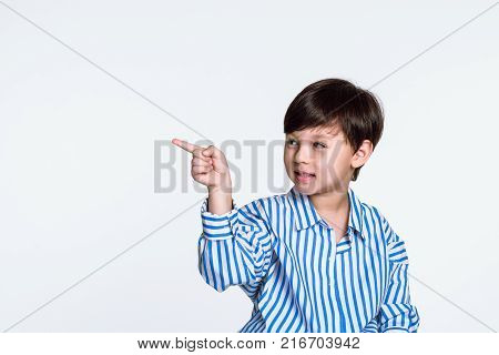 Studio portrait of a boy pointing at something with a finger