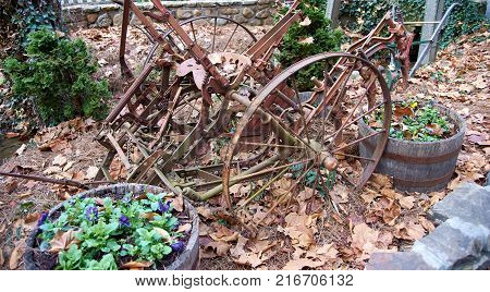 Rustic old machine rotting in pile of leaves