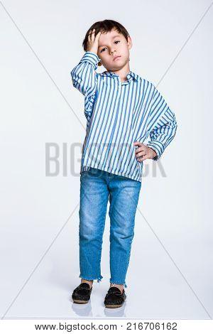Studio full body portrait of a boy having serious worries