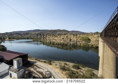 The Douro River at the location of the abandoned truss road-rail bridge with the rail track above the roadway in Pocinho Douro region Portugal