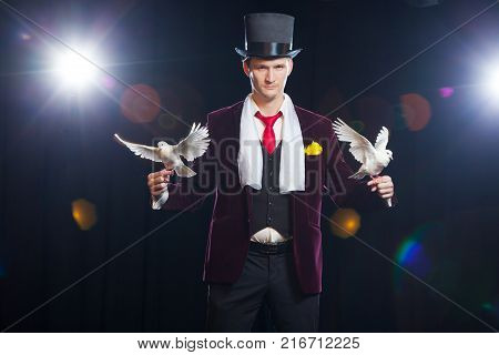 The magician with a two flying white Doves. on a black background.