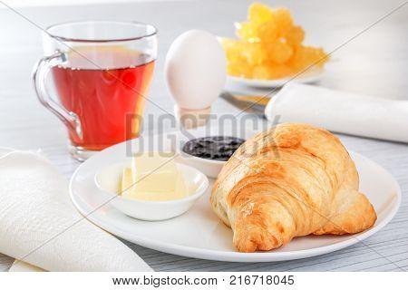 Croissant, boiled egg, tea, butter, jam. Cutlery, napkin. Continental French breakfast. Lightings light