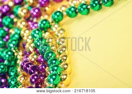 Mardi Gras beads on yellow background with copy space. Close up with shallow depth of field.