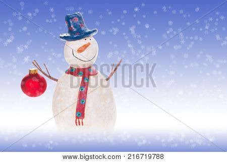 Decorative snowman holding a red Christmas ornament. Blue and white background with snowflakes.