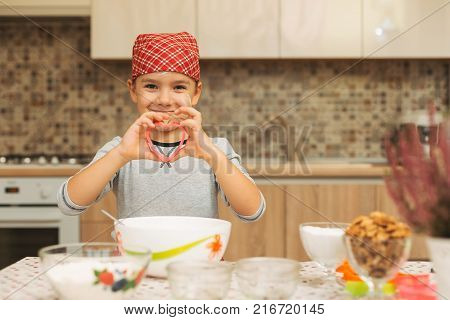 Cute boy shef showing his love while cooking holding a heart form for biscuits in his hansa and smiling. Child hold cookie form in form of heart.