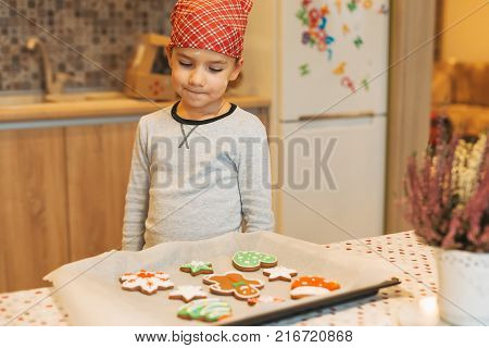 Cute boy anticipating how tasty are fresh baked Christmas biscuits. Cute kid wants to eat Christmas cookies. Child looking to colorful cookies on baking tray.