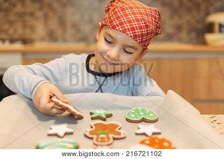 Happy boy anticipating how tasty are fresh baked Christmas biscuits holding one in hand. Cute boy chef enjoying perfect taste of fresh baked Christmas cookies.