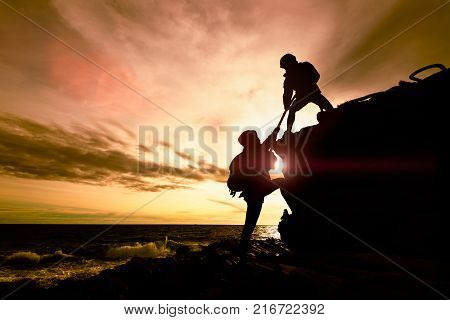 Silhouette of couple helping each other while climbing up on rocks beach in sunset. The concept of aid.