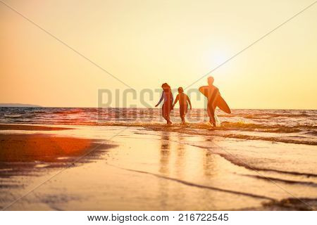 Silhouette of Young surfers with brethren they're relaxing on sunset beach. Summer activity of people on the beach concept. Extreme sports concept.