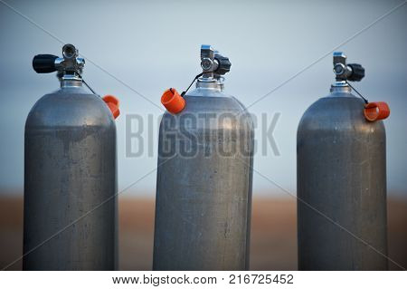 Collection of grey scuba diving air oxygen tanks waiting lined up.