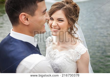 Attractive bride and groom on wedding day. Beautiful newlyweds smiling near the lake. Close-up portrait
