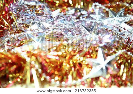 Background festive abstract for Christmas and New Year with tinsel silvery stars and bokeh effect.