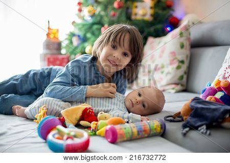 Six Years Old Preschool Boy, Playing At Home With His Newborn Baby Brother