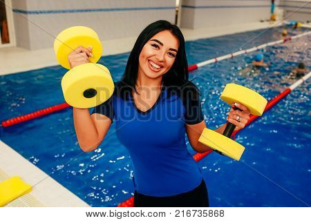 Sporty woman holding foam water dumbbells at swimming pool and positive looking at camera. Aqua aerobics instructor