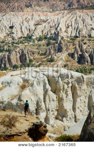Hiker taking in the view of the lunar landscape of the Cappadocia region near Goreme Turkey poster
