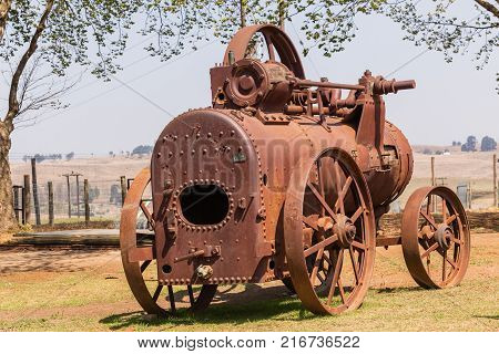 Steam tractor vehicle monument relic with 1914 plate date of manufacture for transport farmlands landscape.