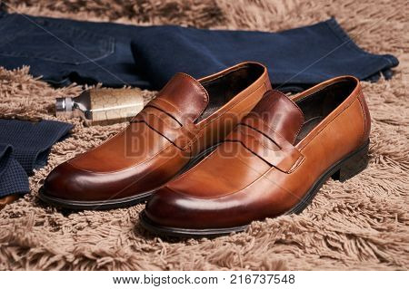 Men's casual clothes and accessories, brown leather shoes, dark suit jacket, vintage purse, denim pants and perfume on the carpet floor, mens fashion set close-up