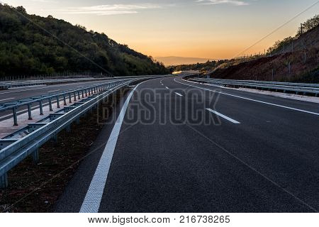 Empty Highway road with markings at sunset