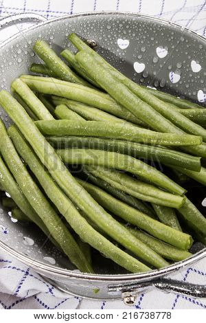 washed and wet green beans in a colander