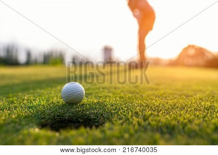 Golfer asian woman putting golf ball on the green golf on sun set evening time select focus. Healthy and Lifestyle Concept.