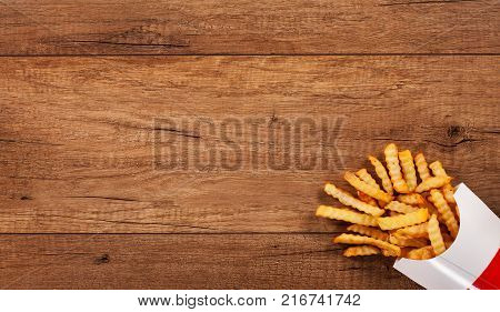 French fries on wooden table spilling from paper bag - large copy space