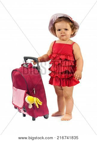 Little girl in red dress ready to travel - standing beside a luggage isolated