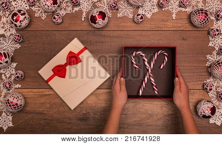 Child hands with christmas gift box containing candy canes - top view inside a seasonal decorations frame