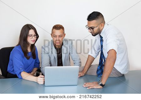 Serious concentrated young executives connecting business partner via laptop using video conferencing. Thoughtful colleagues preparing presentation. Startup concept