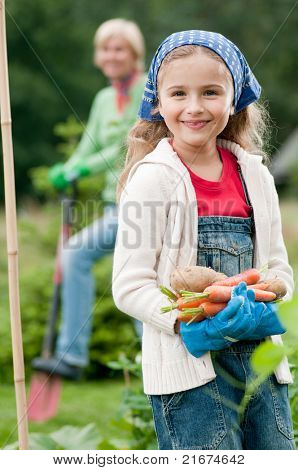 Gardening - little girl with mother working in vegetable garden