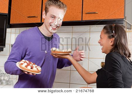 Young couple starting a cream pie fight in the kitchen