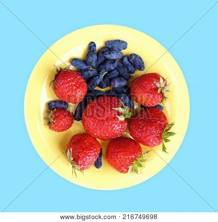 Strawberries and honeysuckle in a plate on a blue background. Top view. Close up.