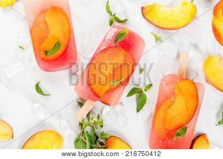 Summer desserts. Frozen drinks. Sweet fruit popsicles from frozen peach tea with mint. On a white marble table with ingredients - peaches mint ice. Copy space