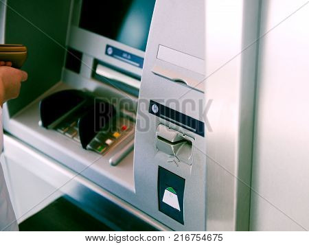 Woman Using Atm Automatic Teller Machine Cash Machine To Enter The Security Pin And Retrieve Withdra