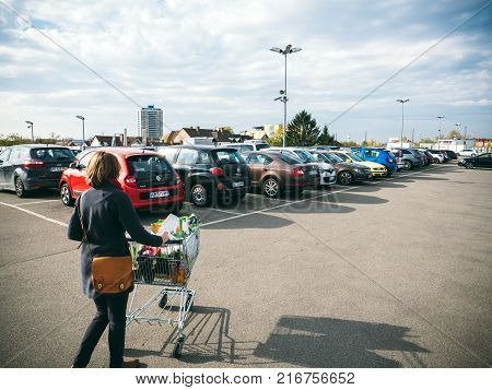 FRANKFURT GERMANY - NOV 4 2017: Elevated view of woman pushing supermarket cart full with food and household products tot he car parked on the roof parking