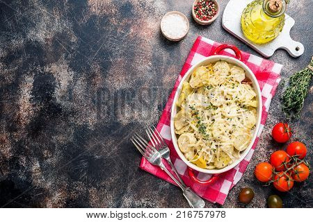 Potato gratin, in rustic dish. Delicious sliced potatoes with onions, tomato, garlic, herbs and chicken meat. top view with copy space