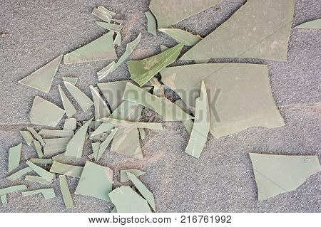 Close up shattered light green plastic sheet on ground