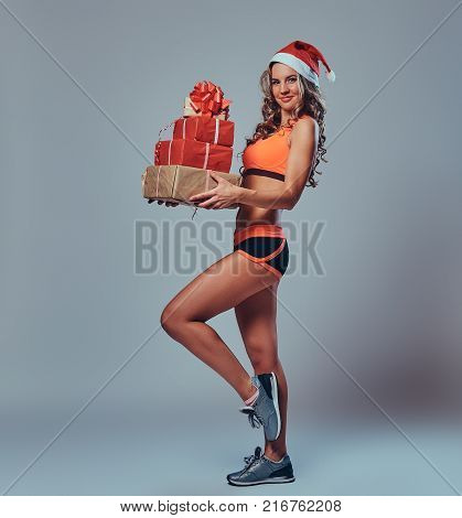 The full body image of blond sporty female in Santa hat holds Christmas gifts over grey background.