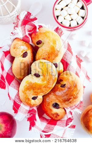 Traditional swedish buns in christmas setting. A saffron bun, in Swedish lussebulle or lussekatt.