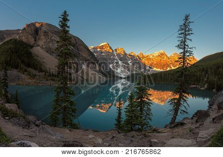Panorama of beautiful sunrise under turquoise waters of the Moraine lake with snow-covered peaks above it in Banff National Park, Canada.