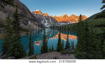Beautiful sunrise under turquoise waters of the Moraine lake with snow-covered peaks above it in Banff National Park, Canadian Rockies.