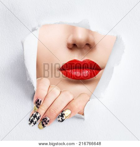 Woman with red lips breaks through slit of white paper. Advertising. Make-up concept.