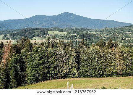 highest hill of Moravskoslezske Beskydy mountains - Lysa hora hill from meadow near Kuncice pod Ondtejnikem village in Czech republic during nice day with clear sky