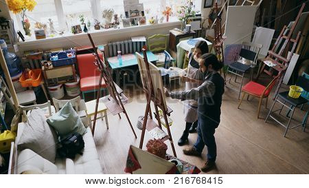 Skilled artist man teaching young girl painting on easel at art school studio - creativity, education and art people concept