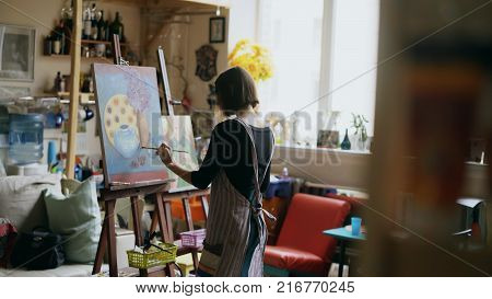 Rear view of Young painter girl in apron painting still life picture on canvas in art-class indoors