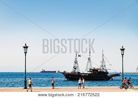 Thessaloniki, Greece - September 14, 2017: Amazing view of seafront with walking people and Thermal Bay in Thessaloniki, Central Macedonia, Greece. Tourist ship in Thessaloniki port