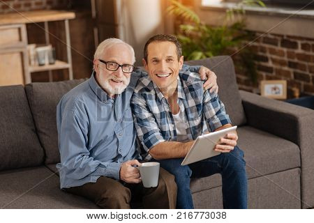 Sweet bonding. Cheerful elderly man sitting on the sofa next to his adult son, hugging him and posing together with him for the camera while bonding to each other