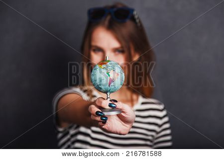 Cheerful girl holding passport, plane ticket and globe before grey background, indoor travel concept